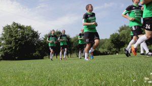 Mehrere Fußballspieler joggen im Trikot der Gold-Kraemer-Stiftung über eine Wiese im Park.