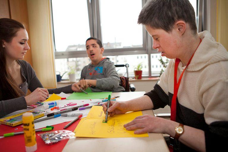 An einem Tisch sitzen drei Personen, die dabei sind mit bunten Stiften eine Karte zu beschreiben. Die Frau links im Bild unterstützt die zwei Männer dabei.