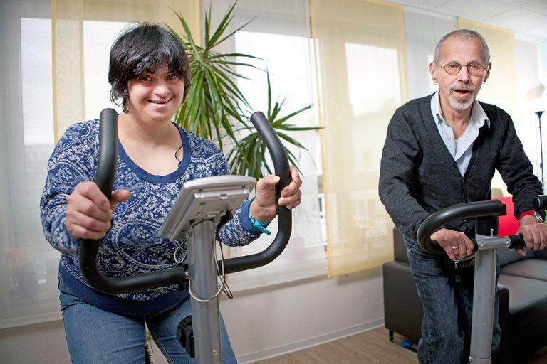 Eine Frau und ein Mann bewegen sich auf zwei Hometrainer Fitnessgeräten.