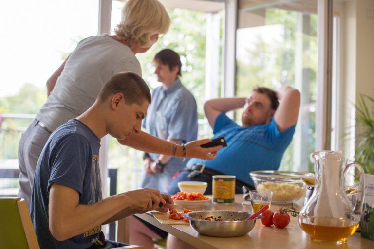 Es befinden sich mehrere Personen in einem Raum in dem ein Tisch steht auf dem Zutaten für ein Gericht stehen. Ein Mann ist dabei Tomaten zu schneiden.