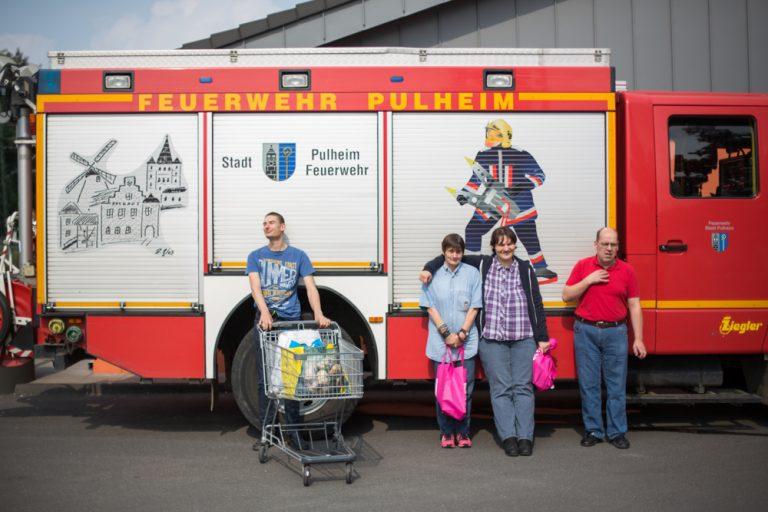 Vor einem Feuerwehrwagen der Stadt Pulheim stehen vier Personen. Einer von ihnen hat einen Einkaufswagen vor sich.