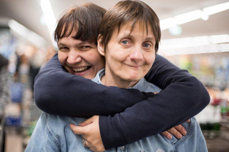 Eine Frau umarmt ihre Freundin von hinten und lacht freudig.