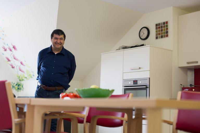 In einer Küche im Paul-Kraemer-Haus Pulheim steht ein Mann hinter dem Esstisch.