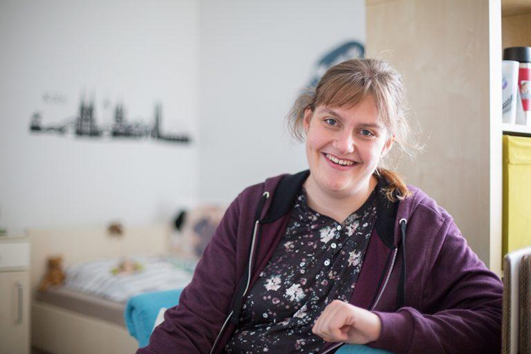 Eine Frau sitzt in einem Schlafzimmer vor dem Bett und lacht in die Kamera.
