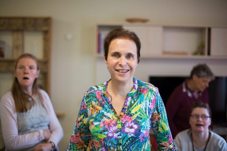 Eine Frau mit blauen Augen und einer bunten Bluse steht frontal zur Kamera. Hinter ihr sind weitere Personen in einem Raum.