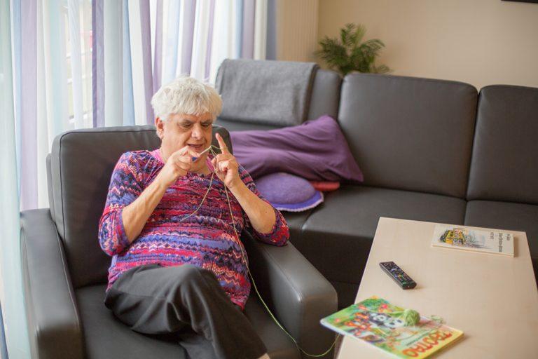 Eine Dame sitzt in einem Sessel in einem Wohnzimmer und ist dabei mit einer grünen Wolle etwas zu häkeln.