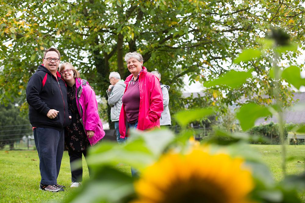 Fünf Personen stehen in einem Garten und genießen die frische Luft. In dem Garten gibt es Sonnenblumen und einen großen Baum.