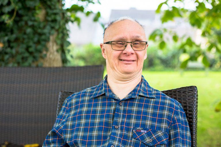 In einem grünem Garten sitzt ein Mann in einem Korbstuhl und schaut in die Kamer. ER trägt ein kariertes Hemd und eine Brille.