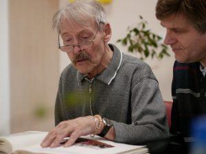 Zwei Männer sitzen am Tisch und blättern in einem Fotoalbum.