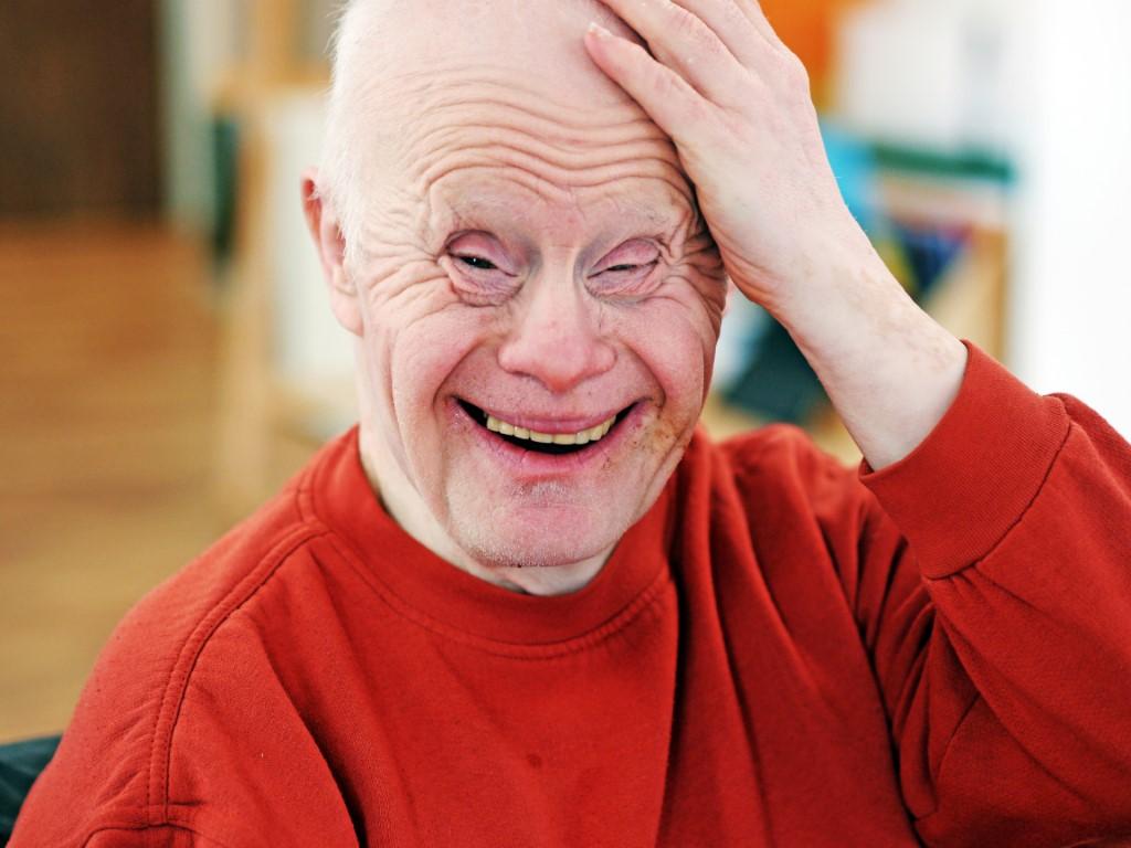 Ein älterer Mann fast sich mit der linken Hand an den Kopf und grinst in die Kamera. Er trägt einen roten Pullover und wirkt sehr glücklich.