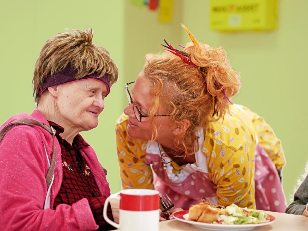 Aufnahme von zwei Frauen in einem besonderen Moment während des Essens. Das Bild ist Titelbild der WIR im Juni 2019 gewessen.