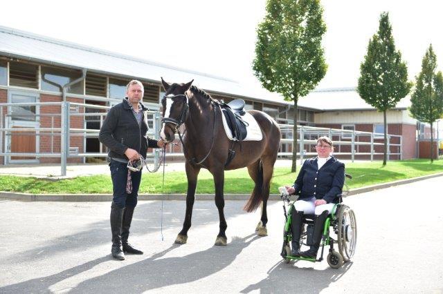 Auf dem Hof steht ein gesatteltes Pferd, das festgehalten wird. Daneben sitzt die Reiterin im Rollstuhl. Sie trägt Turnierkleidung.