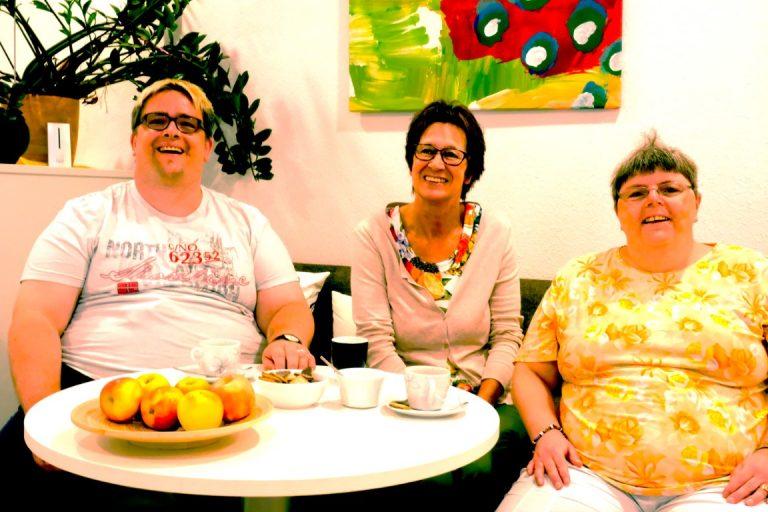 Zwei Frauen und ein Mann sitzen auf einer Bank an einem runden Tisch auf dem Äpfel und Kaffeetassen stehen. Alle drei lachen in die Kamera