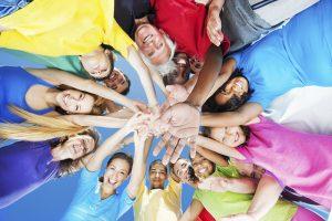 Viele diverse Menschen stehen in einem Kreis und halten die Hände in der Mitte zusammen. Die Perspektive ist von unten nach oben mit Blick in den Himmel.