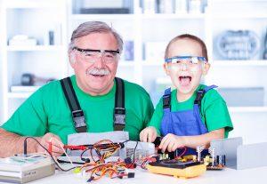 Der ältere Mann und das Kind tragen Schutzkleidung. Beide sehen sehr fröhlich aus. Sie führen ein Physikexperiment durch.