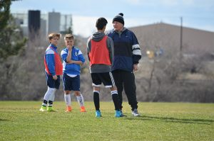Der Trainer steht mit drei Jungs in Fußballkleidung auf der Wiese und sie unterhalten sich.