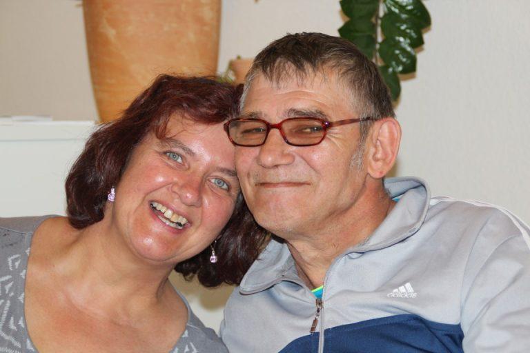 Eine Frau lehnt ihren Kopf an den eines Mannes. Beide sehen sehr glücklich und zufrieden aus.
