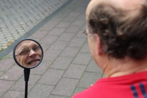 In der über die Schulter Perspektive fotografiert in einen Rückspiegel sieht man das Gesicht eines Mannes, sowie seinen Hinterkopf und den Nacken.