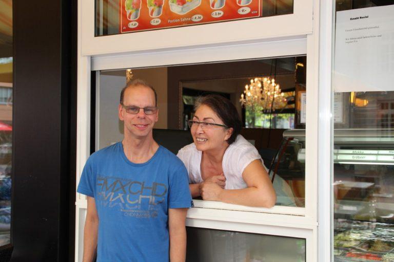 Eine Frau lehnt sich aus dem Ausgabefenster einer Eisdiele hervor. Ein Mann steht vor dem Fenster und lächelt in die Kamera.