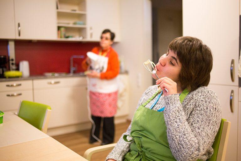 Eine Frau mit Schürze leckt den Teig von einem Rührbesen ab. Sie sitzt in der Küche. Im Hintergrund trocknet eine Frau Geschirr ab.