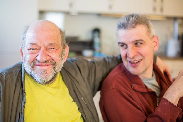 Zwei Männer sitzen in der Küche und halten sich im Arm.