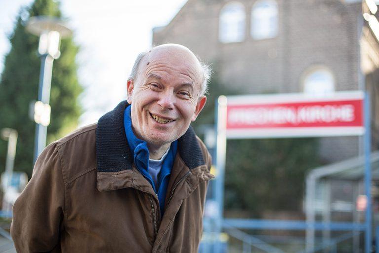 Ein Mann lacht in die Kamera. Er befindet sich an einer Straßenbahnstation.