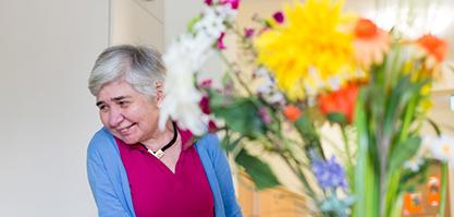 Hinter einem Blumenstrauß schaut eine Frau verlegen hervor.