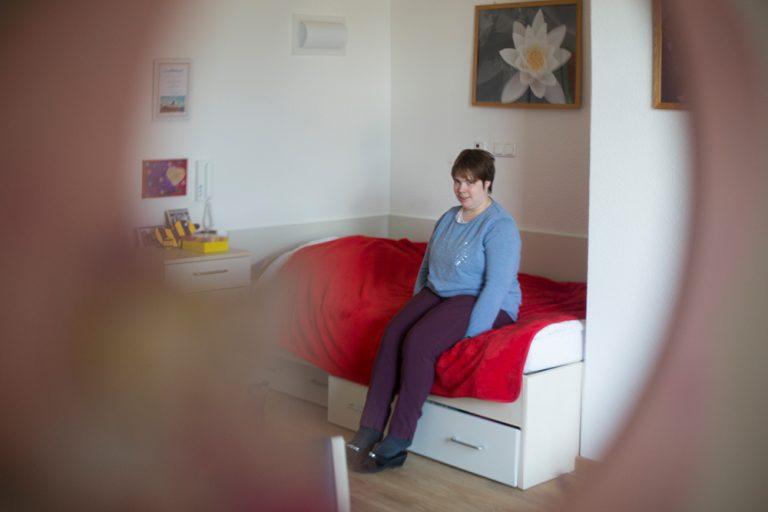 Eine Frau sitzt in gemütlicher Kleidung auf dem Bett, daneben ist ein Nachtisch mit einigen persönlichen Sachen darauf.
