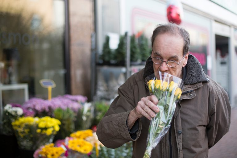 Ein Mann riecht an einem Strauß gelber Rosen. Er steht vor einem Blumenladen auf der Fußgängerzone.