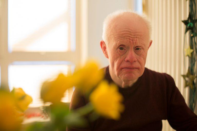 Ein älterer Herr schaut etwas kritisch in die Kamera. Im Vordergrund sind gelbe Blumen in Unschärfe.