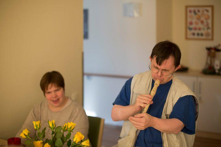 Ein Mann spielt Blockflöte und eine Frau hört ihm dabei zu.