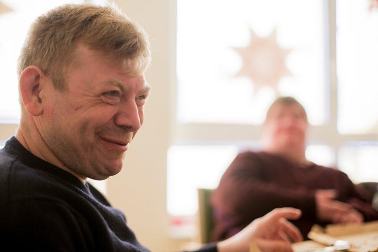 Ein Mann ist im Profil fotografiert, wie er lächelt. Er sitzt zusammen mit einer Frau in einer Runde am Tisch.