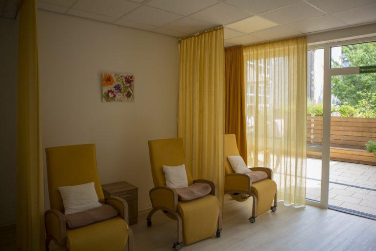 Ein Raum in dem jeweils mit Kissen und Decke ausgestattet drei gemütliche Sesel stehen. Dazwischen sind Vorhänge angebracht. Alles ist in gelb und orange Tönen gehalten.