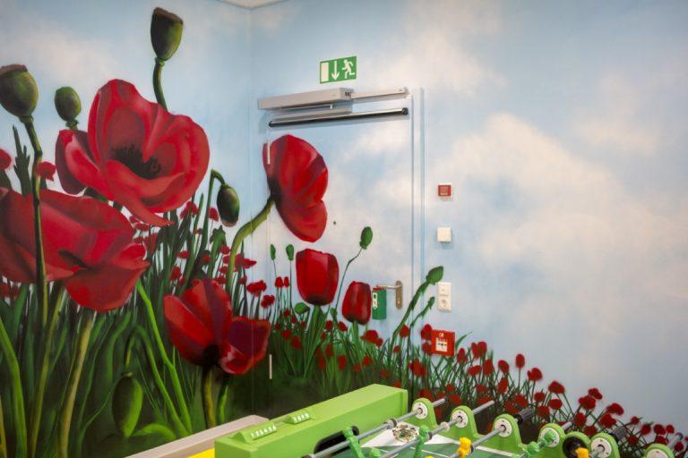 An der Wand und über die Tür sind große Mohnblumen wie auf einem Feld mit blauem Himmel gemalt. An der unteren Kante ist ein Tischkicker zu erkennen.
