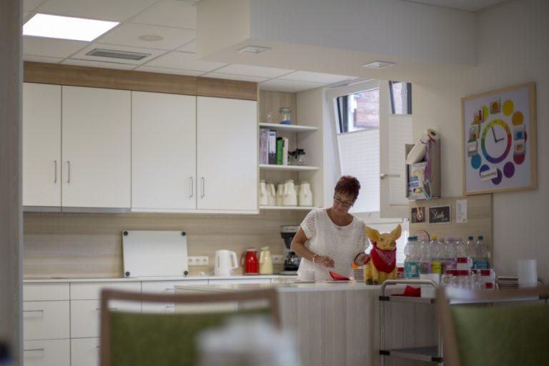 Eine Frau steht hinter dem Thresen in einem Gemeinschaftsraum bzw. einer Küche. Kaffekannen, Wasserflaschen und ein Servierwagen stehen bereit.