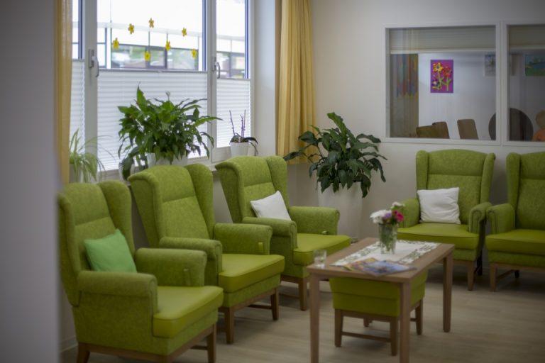 Ein Raum, in dem mehrere grüne Sessel und ein Beisteltisch stehen. Auf der Fensterbank und in der Ecke stehen Zimmerpflanzen