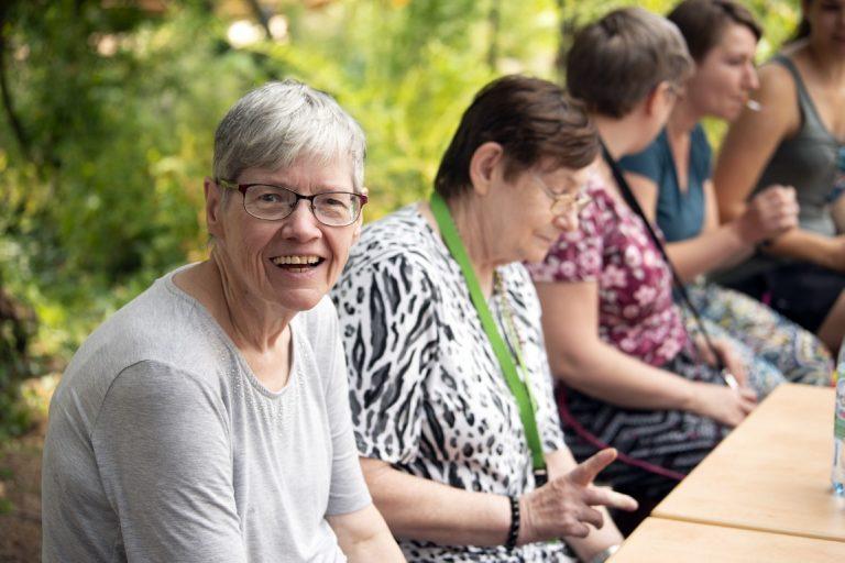 Mehrere Frauen sitzen in einer Reihe an einem Tisch. Im Fokus ist eine ältere Dame, die in die Kamera lächelt.