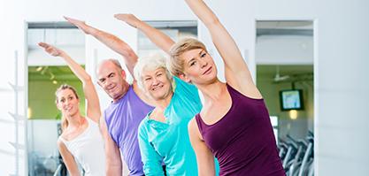 Eine Gruppe von Senioren steht hintereinander und alle dehnen sich in die selbe Richtung.