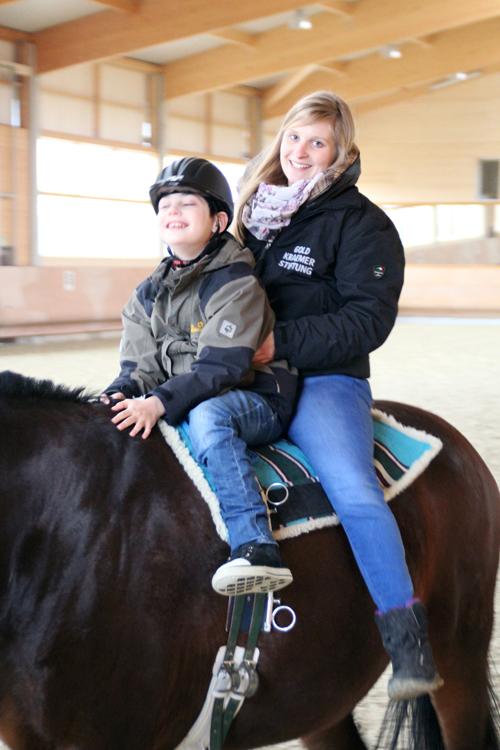 Auf dem Rücken eines dunkelbraunen Pferdes sitzen ein Junge und eine Mitarbeiterin, die den Junge vor ihr festhält.