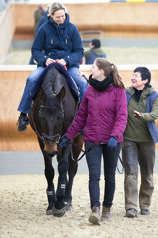 Auf einem Pferd, das in der Reithalle geführt wird sitzt eine Frau. Sie wird geführt, daneben läuft eine weitere Person, die die Reiterin am Oberschenkel hält.