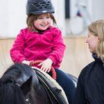 Ein kleines Mädchen in pinker Jacke sitzt auf einem kleinerem Pferd das von einer Trainerin in der Reithalle geführt wird.