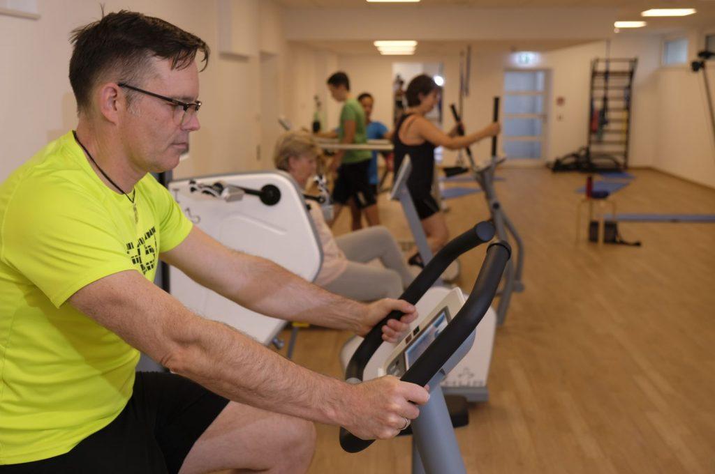 Im Vordergrund ein Mann im gelben T-Shirt, der ein Sportgerät nutzt. Im Hintergrund unscharf: weitere SportlerInnen während des Trainings.