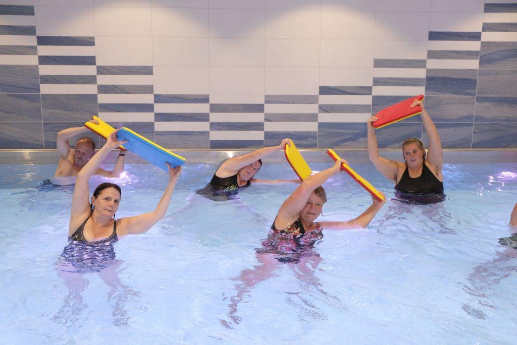 Teilnehmer*innen an einem Aqua-Sport Angebot befinden sich im Schwimmbecken und halten ein Schwimmbrett über den Kopf und strecken sich nach links und rechts.