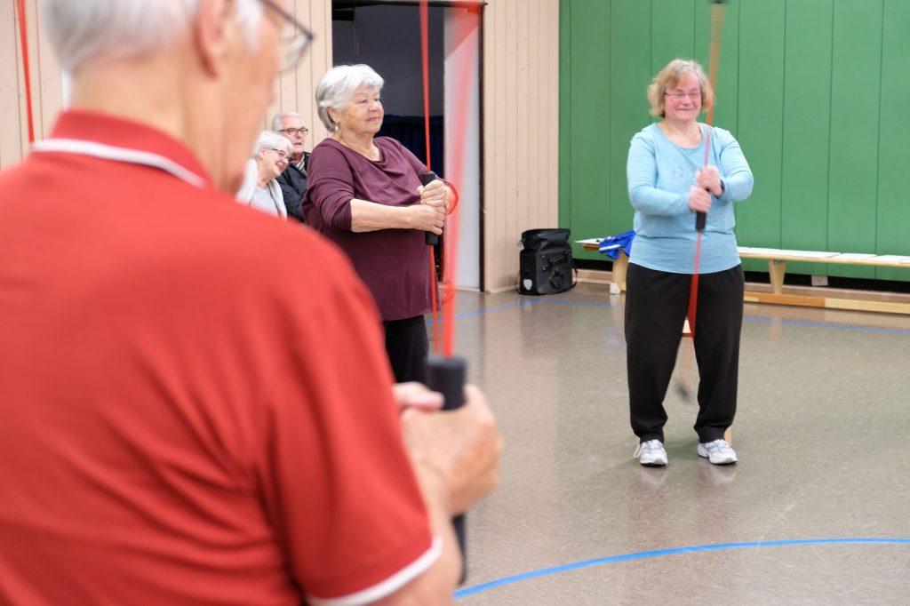 Drei Reha-Sport-Teilnehmer*innen stehen in der Turnhalle im Kreis und halten einen Schwingstab vor dem Körper.