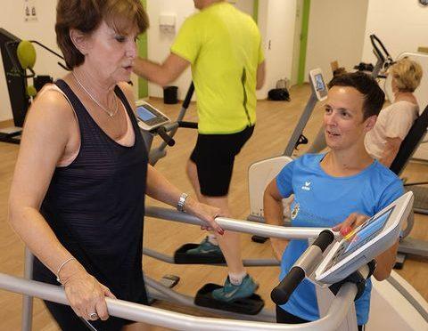Eine Frau steht im Fitnessstudio auf einem Gerät und eine Trainerin steht dabei. Im Hintergrund sind zwei Sportler*innen beim Training.