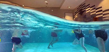 Querschnitt des Schwimmbeckens. Blick unter Wasser, indem Unterkörper in Bewegung sind.