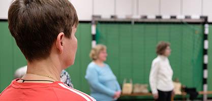 Über die Schulter eines Teilnehmers in der Turnhalle fotografiert stehen Teilnehmende im Kreis.