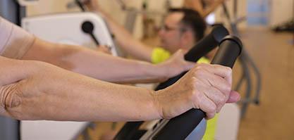 Die Hände einer Sporttreibenden Person greifen an die Griffe eines Sportgeräts im Fitnessstudio.