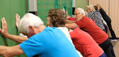 Eine Gruppe von Senioren steht nebeneinander und alle dehnen sich an einer Wand nach vorne.