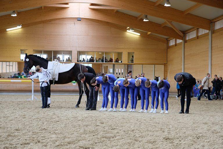 In einer Wettkampfsituation steht ein Team in der Mitte der Reithalle neben dem Voltigierpferd und alle verbeugen sich.